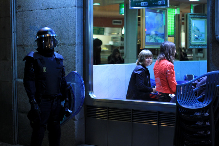portfolio 19/40  - SOCIAL. Una joven observa por la ventana el despliegue policial por una protesta en apoyo al barrio burgalés de Gamonal.
